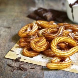 churros with sugar on a paper with a jarr og choclate sauce on the side